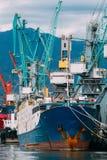 Старые топливозаправщик корабля перевозки баржи и кливер кранов тяжелой загрузки в порте стоковое изображение