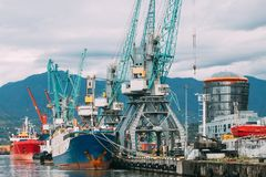 Старые топливозаправщик корабля перевозки баржи и кливер кранов тяжелой загрузки в порте стоковое фото