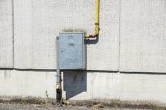 Старые трубы металла воды зафиксированные с кронштейнами перед стеной гипсолита с коробкой металла для счетчика воды Стоковое фото RF