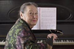 Старые усмехаясь посадочные места пианиста дамы на рояле стоковые изображения rf