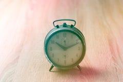 Старые часы на деревянной таблице Стоковые Изображения