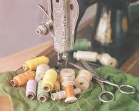 Старые швейная машина, ножницы и катышкы года сбора винограда потока, крупного плана Стоковые Изображения