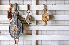 Старые шкивы на белой деревянной стене стоковые изображения