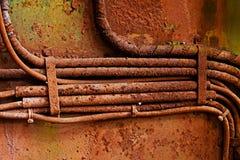 Старые электрические кабели на пакостной ржавой железной стене Стоковые Изображения RF