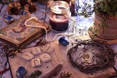 Старые tarot пакет карт, runes и высушенные корни с книгой на таблице стоковое изображение
