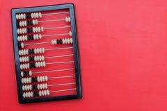 Старый абакус с костяшками на красной предпосылке Стоковое Фото