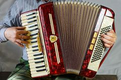 Старый аккордеон потеха, который нужно сыграть в руках пожилого музыканта стоковые изображения