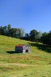 Старый амбар стоит в середине фермы Стоковое Изображение RF