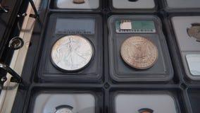 Старый американский серебряный доллар и новый американский серебряный доллар на альбоме для собрания монеток Стоковое фото RF