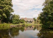 Старый английский исторический коттедж увиденный над озером с отражениями стоковые изображения rf