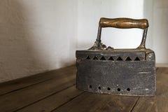 Старый античный ржавый утюг на деревянной полке Стоковая Фотография
