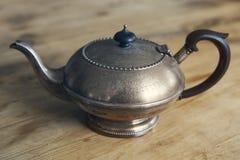 Старый античный чайник на деревянном столе Стоковые Фотографии RF