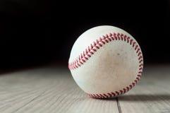 Старый бейсбол на деревянных предпосылке и сильно крупном плане стоковая фотография
