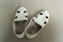 Старый белый ботинок на предпосылке пола цемента Стоковые Фото