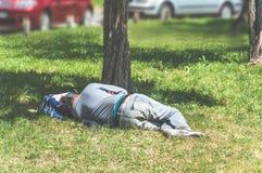 Старый босоногий человек бездомные как или беженца спать на траве в парке города используя его сумку перемещения как подушка, соц Стоковая Фотография RF