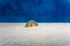 Старый будильник на песке и голубой предпосылке стоковые фото