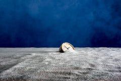 Старый будильник на песке и голубой предпосылке стоковое фото rf