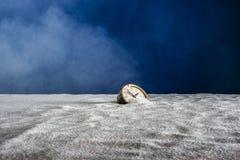 Старый будильник на песке и голубой предпосылке стоковые фотографии rf