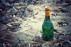 Старый бутылочный зеленый вина лежит на портовом районе в песке Стоковое Изображение RF