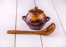 Старый варить бака глиняного кувшина и деревянное sppon на белизне Стоковые Изображения RF