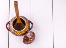 Старый варить бака глиняного кувшина и деревянное sppon на белом деревянном backgrou Стоковая Фотография