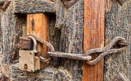 Старый введенный в моду ржавый цепной замок на деревянной двери Стоковое Фото