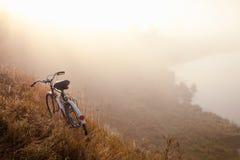 Старый велосипед рано утром в сельской местности и тумане ландшафта стоковое фото rf
