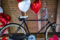 Старый велосипед летая прыгает к воздушным шарам сформированным сердцем Стоковая Фотография RF