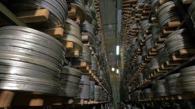 Старый винтажный вьюрок фильма, ленты фильма в случаях лежа на shelfs архива Съемка тележки видеоматериал