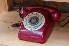 Старый винтажный красный цвет телефона с на предпосылкой деревянного стола Стоковые Изображения