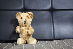 Старый винтажный плюшевый медвежонок сидя на софе Стоковое Изображение