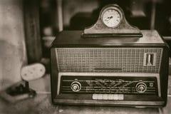 Старый винтажный радиоприемник прошлого столетия с деревенскими часами на верхней части на силле окна - виде спереди, sepia стоковые фотографии rf