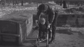 Старый винтажный monochrome человек фильма кладет ребенк в детскую дорожную коляску и пряжки вверх по поясу акции видеоматериалы