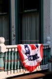Старый, выдержанный экстерьер дома с американским флагом задрапировал над перилами Стоковые Изображения RF