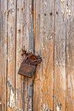 Старый выдержанный padlock grunge ржавый запертый на старой двери деревянной доски Стоковое фото RF