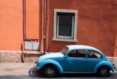 Старый голубой автомобиль на улице на коричневом здании Стоковая Фотография