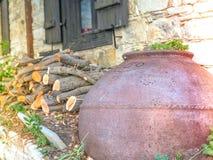 Старый греческий бак стиля для хранить масло и вино и древесина огня подготовил в дворе стоковое изображение