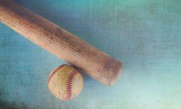 Старый грубый и изрезанный бейсбол и винтажная деревянная летучая мышь на голубой предпосылке текстуры Стоковое Изображение