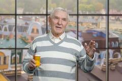 Старый дед с бутылкой пилюлек Стоковые Фото