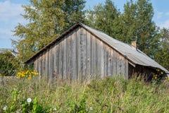 Старый деревянный дом среди травы стоковая фотография rf