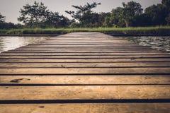 Старый деревянный мост через озеро в глубоком лесе, естественной винтажной предпосылке стоковое изображение