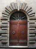 Старый деревянный портал с высекаенным каменным сводом итальянской средневековой крепости стоковое изображение rf