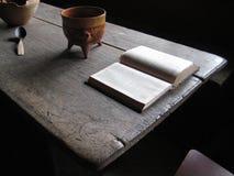 Старый деревянный стол с светом открытой книги спокойным стоковая фотография