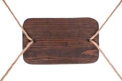 Старый деревянный шильдик темной древесины, вися на веревочках изолировано Стоковые Фотографии RF