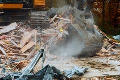 старый дом будучи сокрушанным большим backhoe стоковая фотография rf