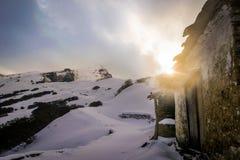 Старый дом в горе покрытой с снегом стоковое изображение