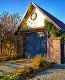 Старый дом с дверями в осени В дворе старым желтого цвета упаденного домом выходит Стоковые Изображения RF