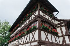 Старый дом с красными гераниумами на окнах Стоковое Изображение