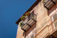 Старый дом с цветками на балконе Стоковая Фотография RF