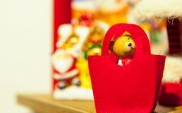 Старый деревянный красный цвет медведя игрушки чувствовал близко рождественской елки на заднем плане другие украшения и гирлянды  Стоковые Фото